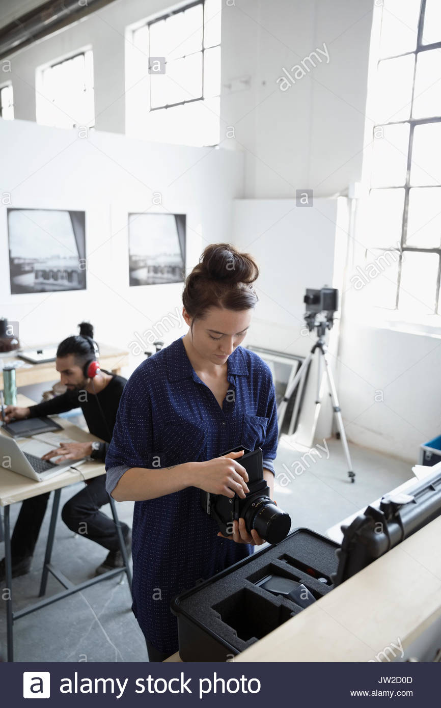 Female photographer working with digital camera and lens in art studio - Stock Image