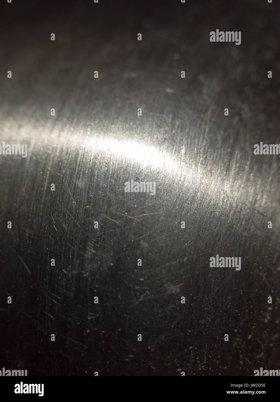 close up scratched metal surface with light across; UK - Stock Image