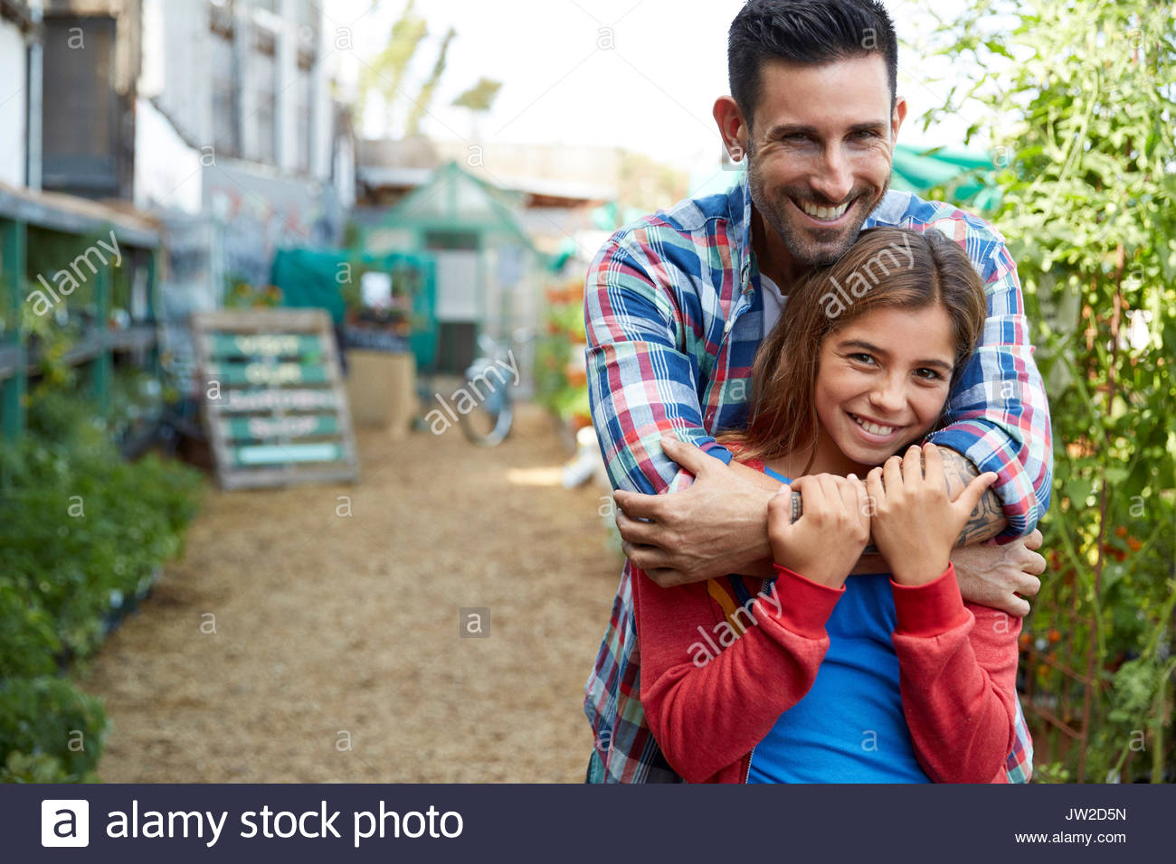 Portrait smiling father and daughter hugging in garden Stock Photo