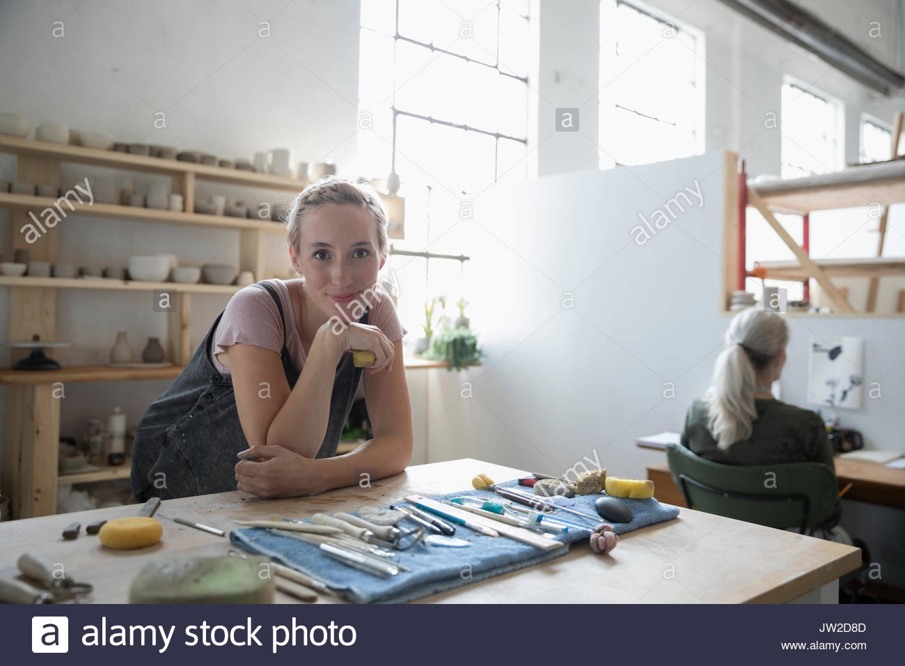 Portrait confident female potter leaning on workbench with tools in art studio - Stock Image