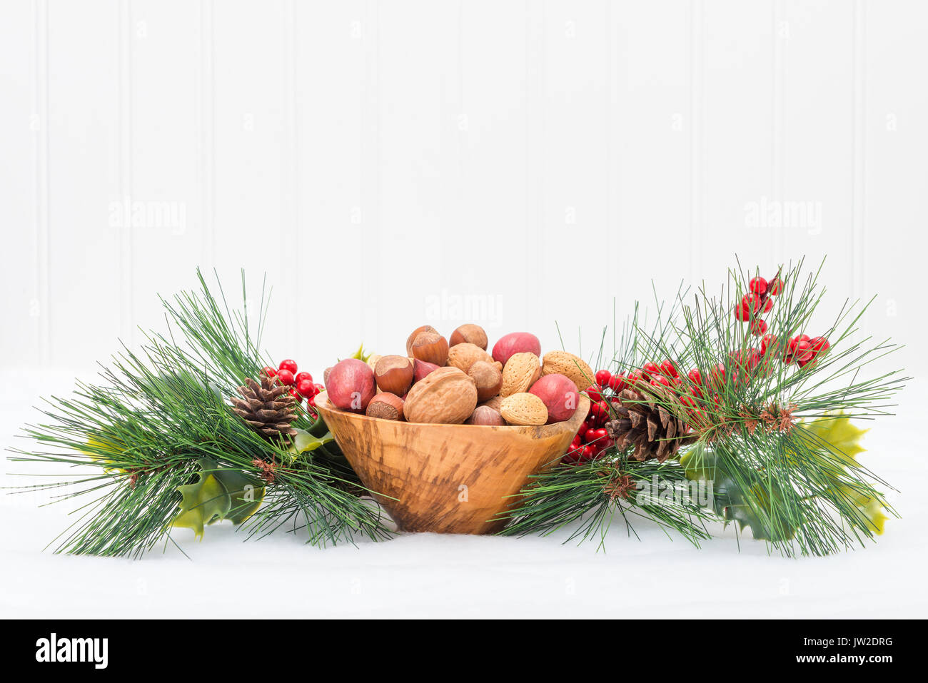Wooden bowl of mixed nuts surrounded by a festive garland. - Stock Image