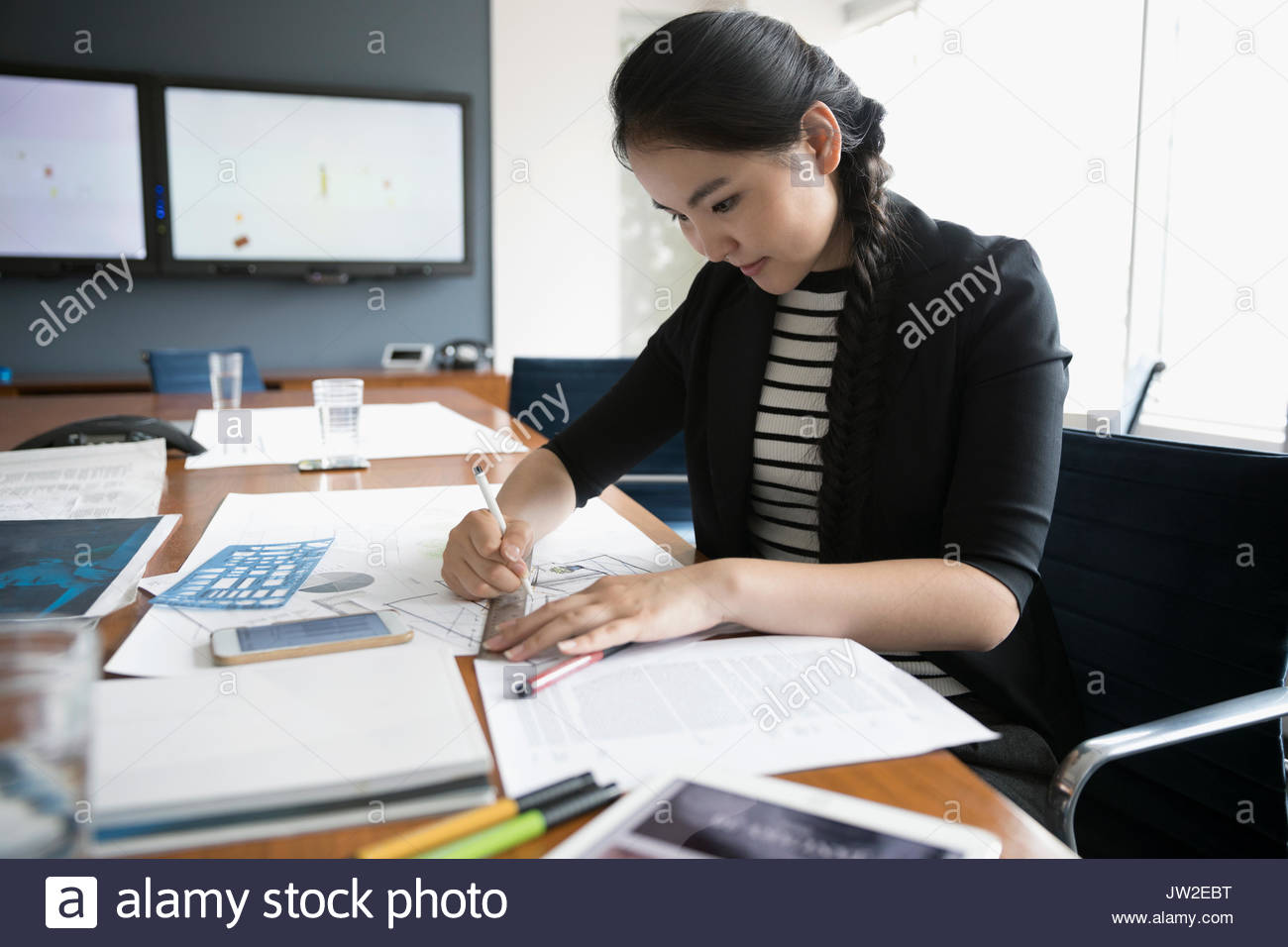 Female architect drafting blueprints in conference room - Stock Image