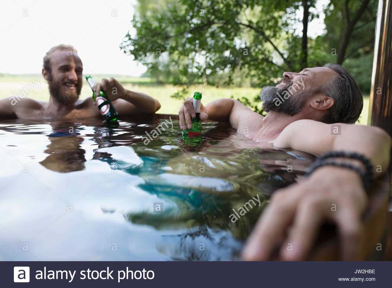 Male friends relaxing, drinking beer soaking in hot tub - Stock Image