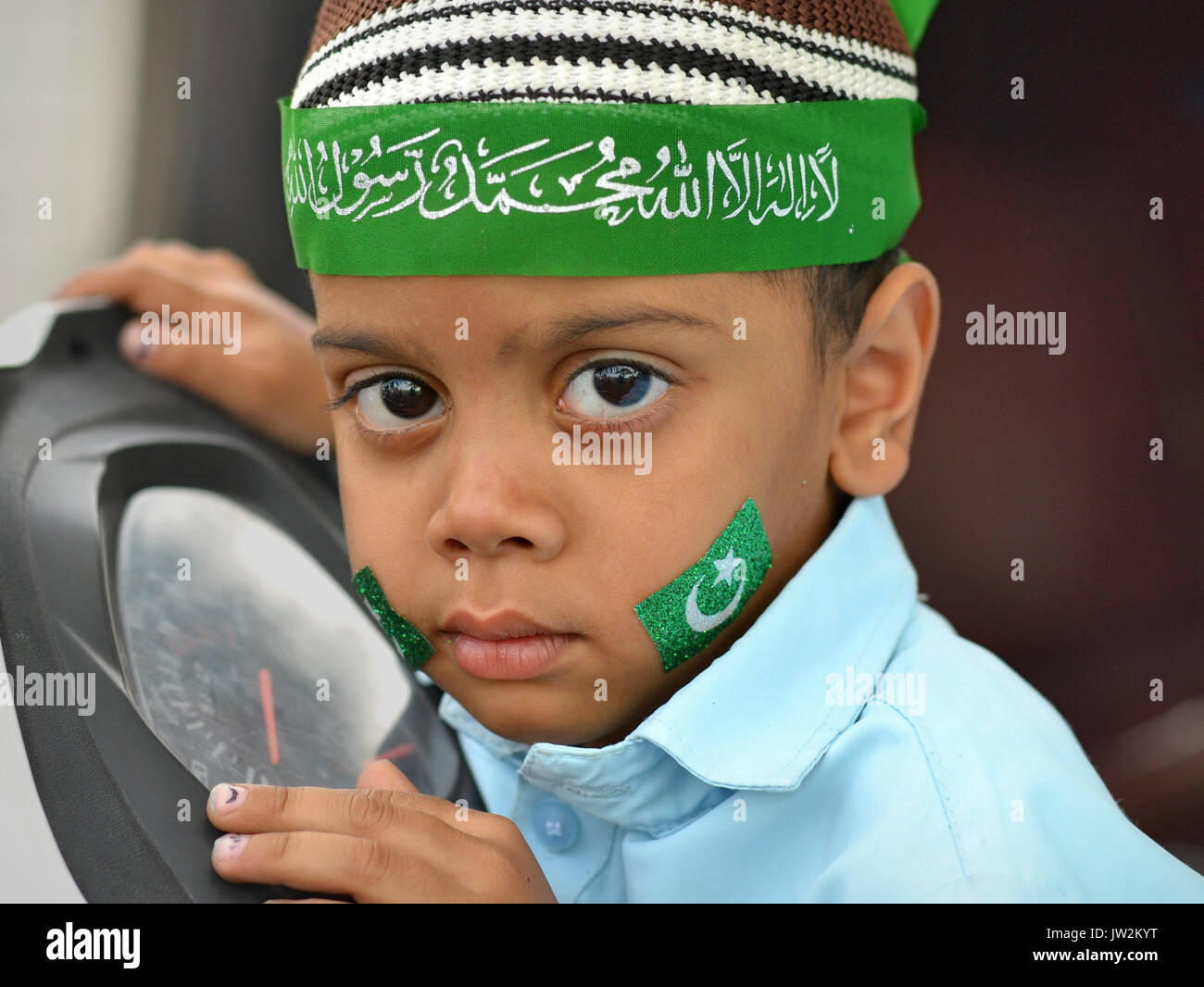 Little Indian Muslim boy, wearing a green bandana during Rabi' al-awwal festivities (Muhammad's birthday) - Stock Image