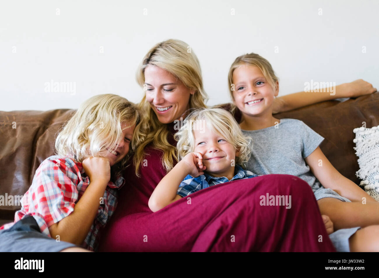 Mother and children (4-5, 6-7, 8-9) resting in living room - Stock Image