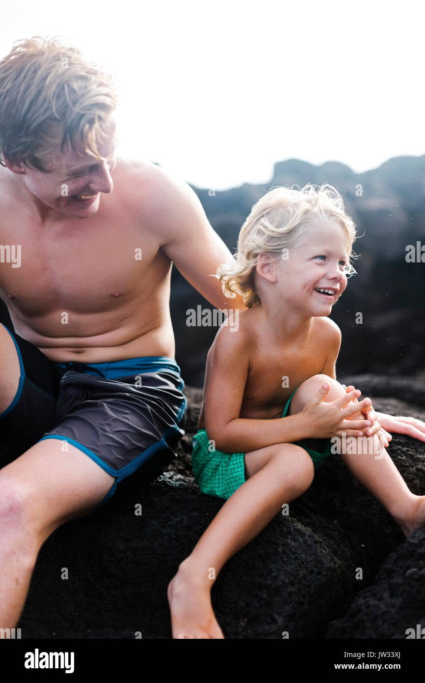 Young man with younger brother (4-5) sitting on rocks - Stock Image