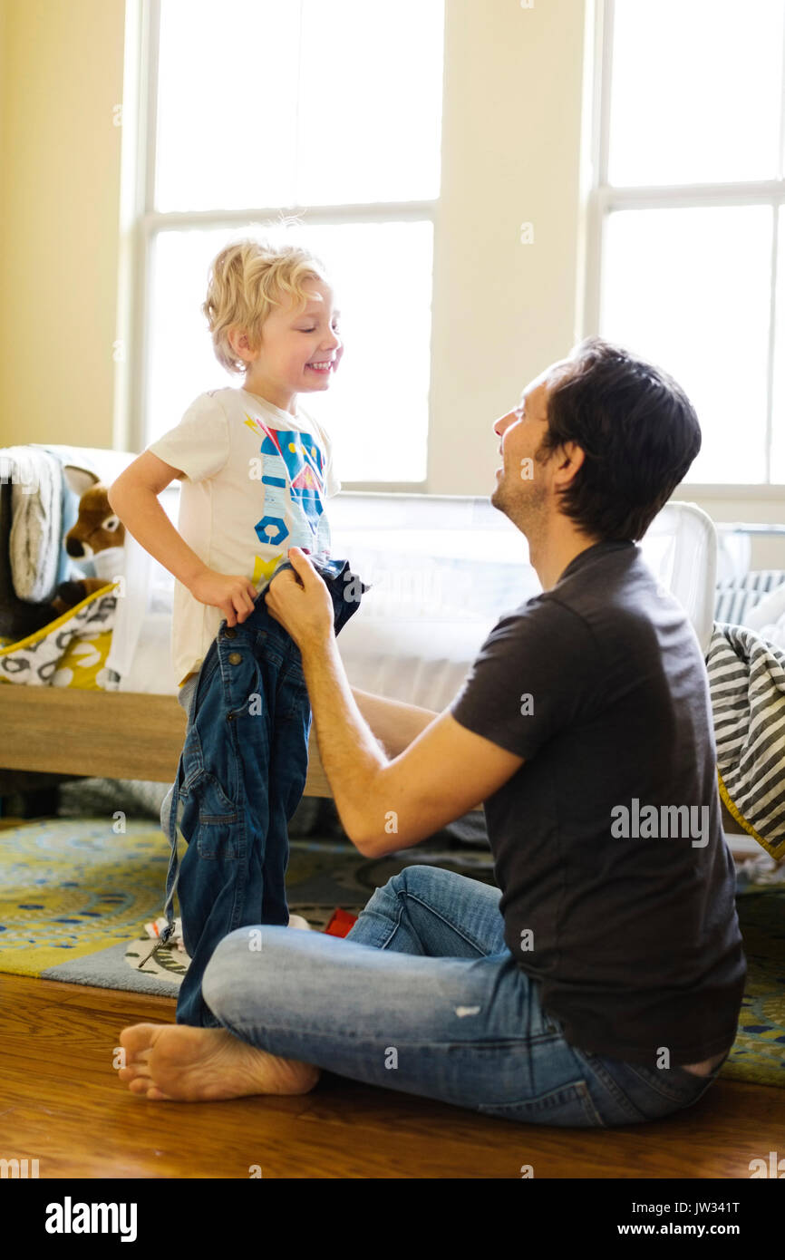 Father assisting son (4-5) with getting dressed - Stock Image