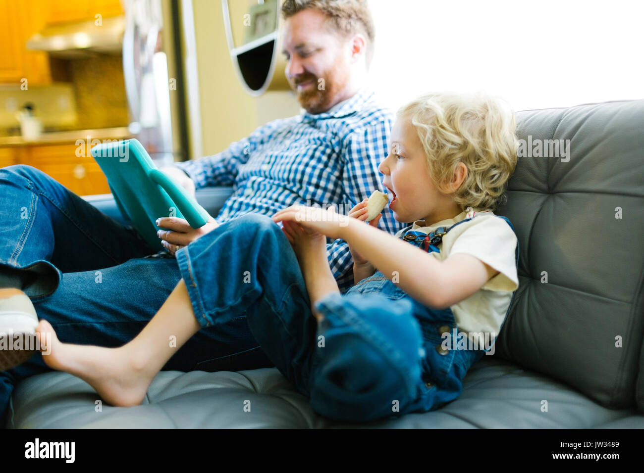 Boy (4-5) and man using digital tablet on sofa in living room - Stock Image
