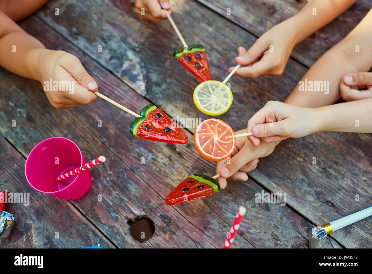 Hands of children with sweets on a wooden  background. - Stock Image
