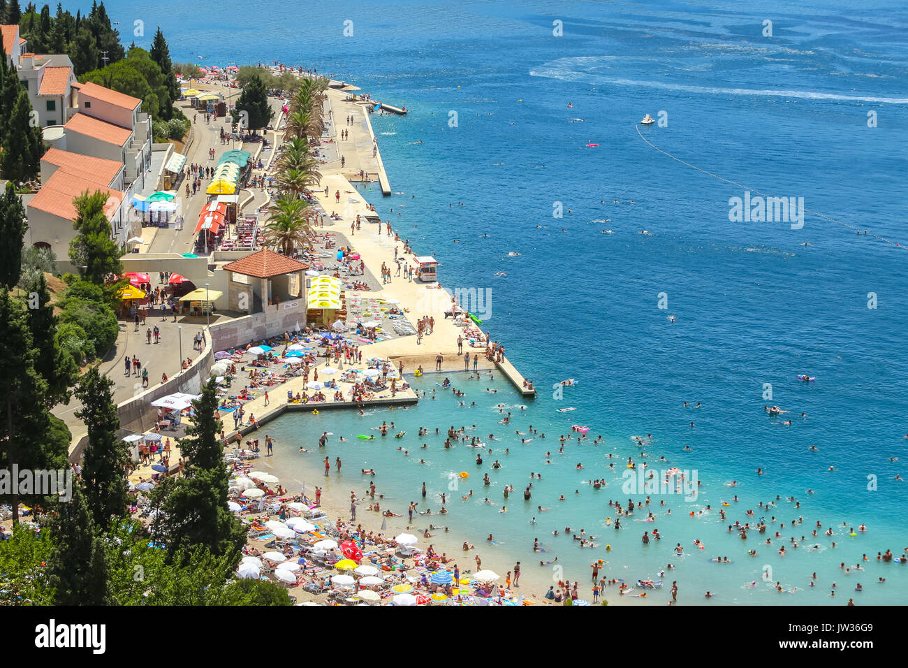 NEUM, BOSNIA AND HERZEGOVINA - JULY 16, 2017 : A view of the town waterfront and people swimming and sunbathing on the beach in Neum, Bosnia and Herze - Stock Image