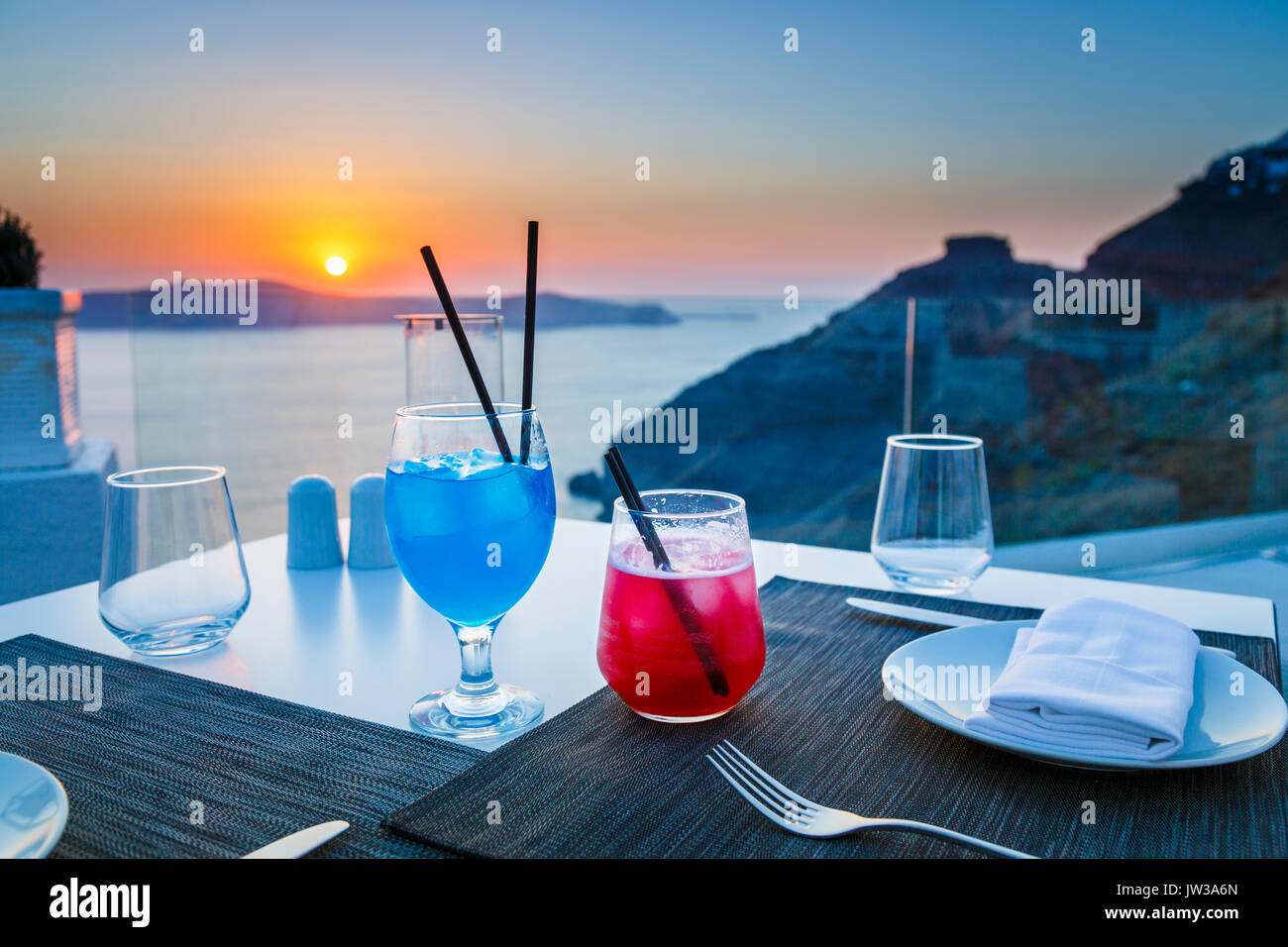 Colourful cocktails, Imerovigli in the evening, a village near Fira on the Greek island of Santorini called 'the - Stock Image
