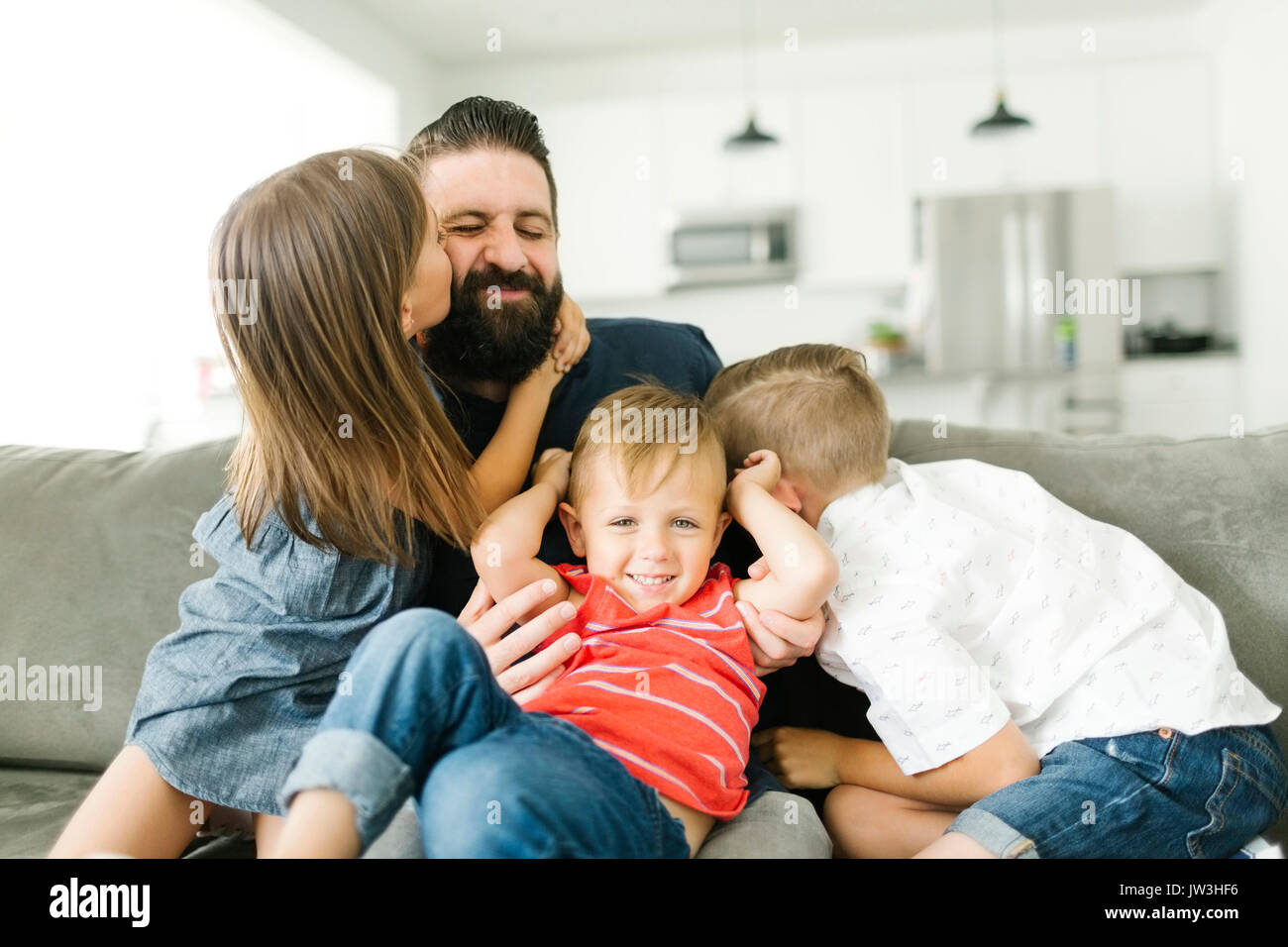 Father playing with his three children (2-3, 6-7) - Stock Image