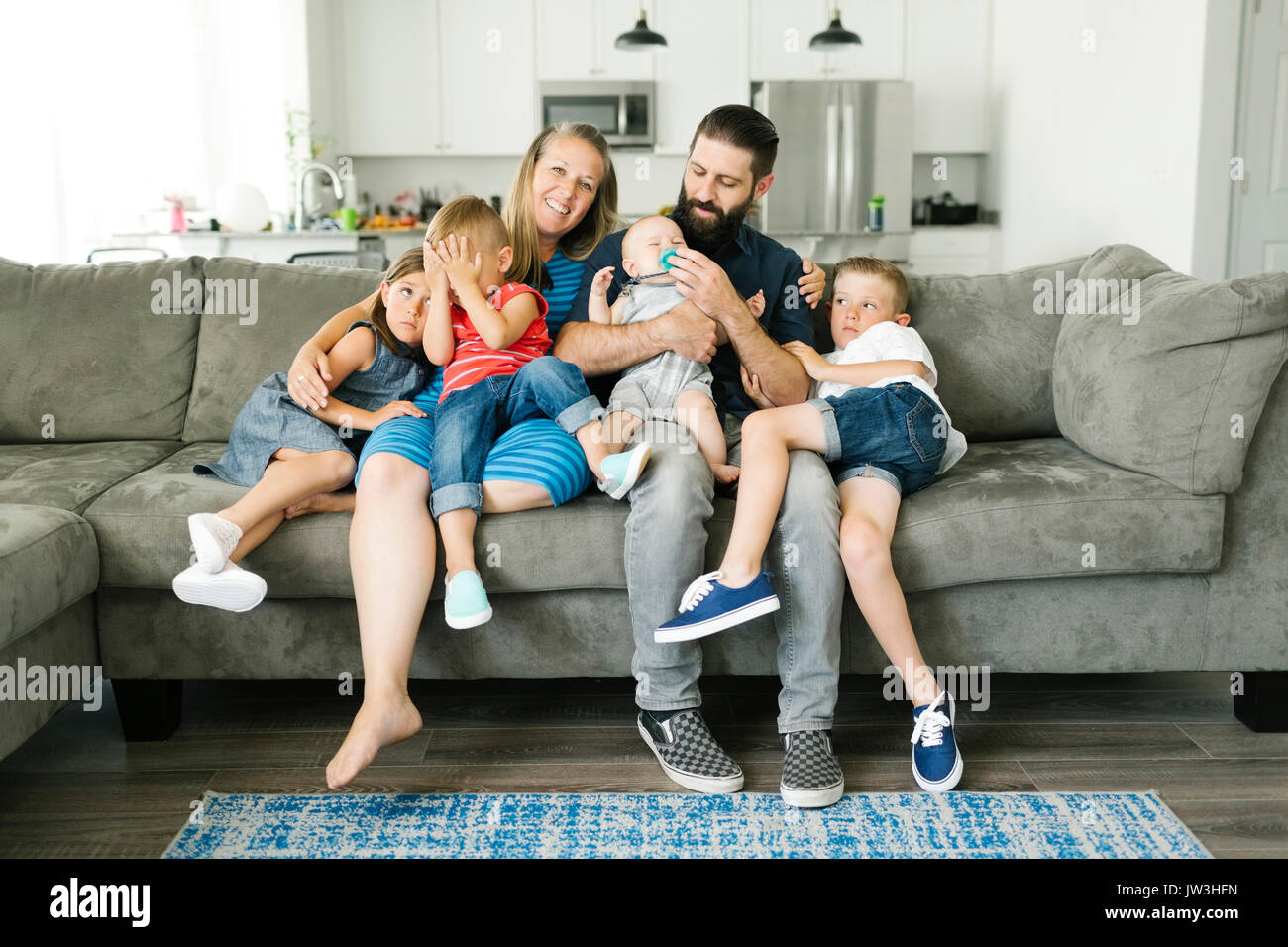 Family with four children (6-11 months, 2-3, 6-7) spending time on sofa - Stock Image