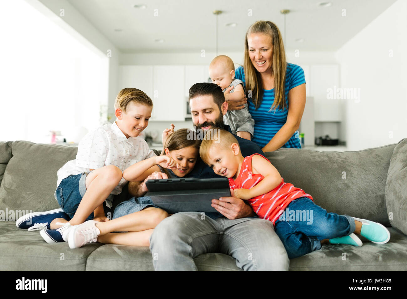 Family with four children (6-11 months, 2-3, 6-7) using digital tablet - Stock Image