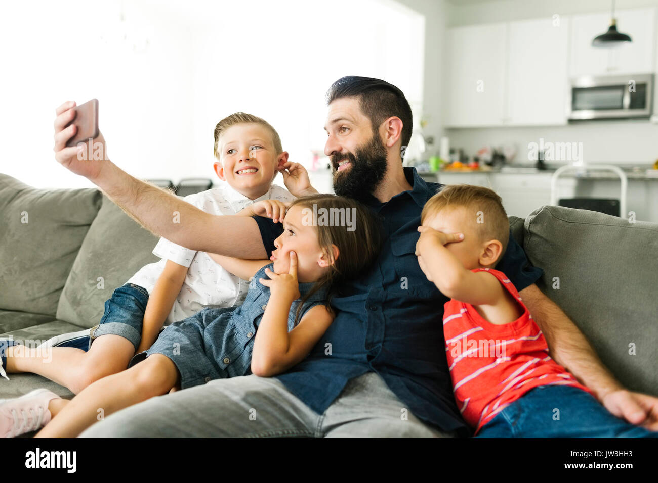 Father with his three children (2-3, 6-7) taking selfie with smart phone - Stock Image