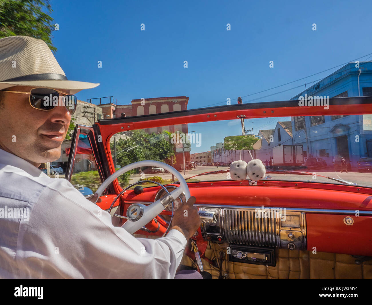Cuban Taxi Driver In Straw Hat And White Shirt At The Wheel Of His 1951 Chevy Steering Red Chevrolet Convertible Driving Through Streets Old Havana With Fuzzy