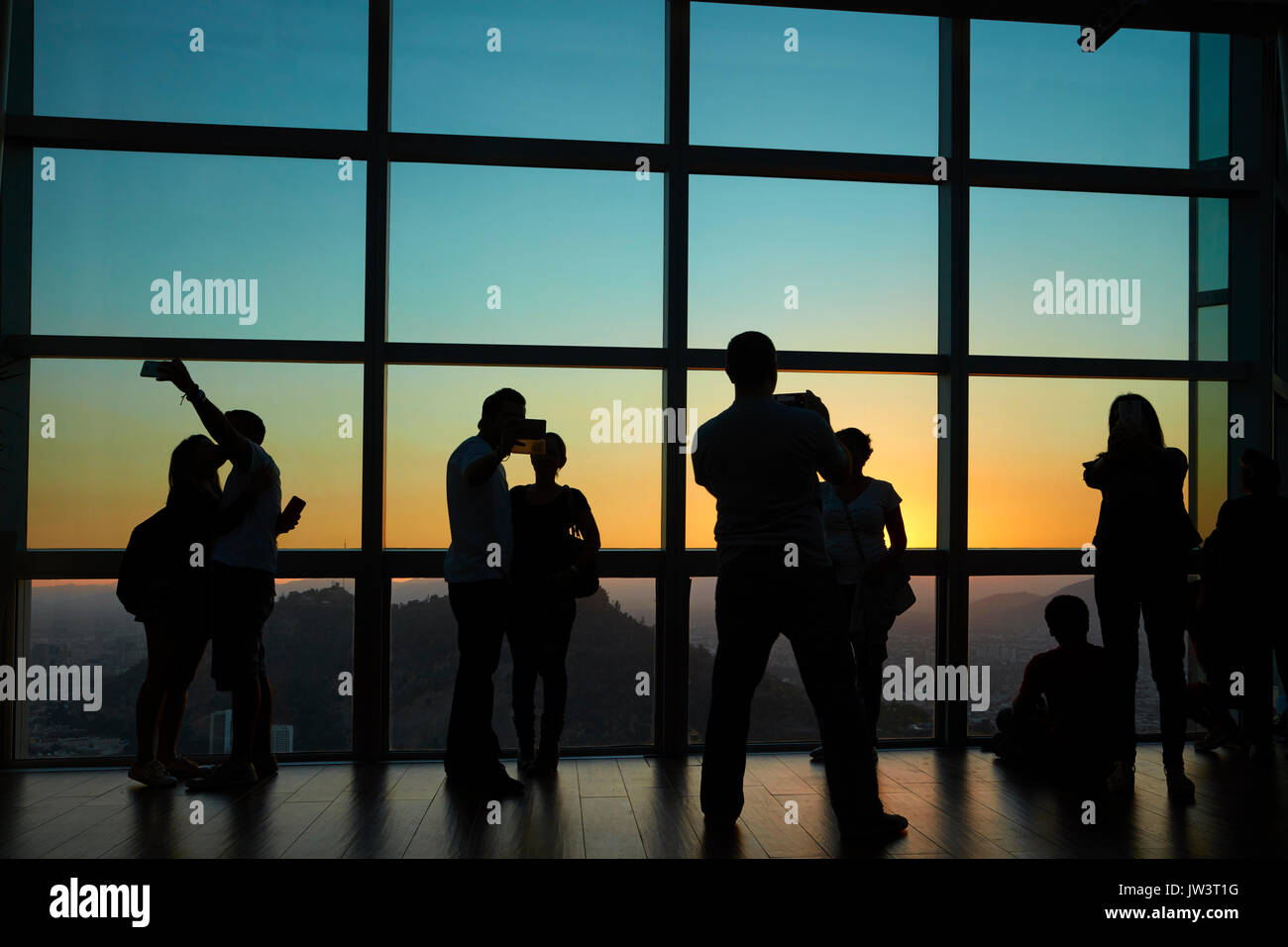 Tourists looking at the view at sunset from Sky Costanera skyscraper, Santiago, Chile, South America - Stock Image