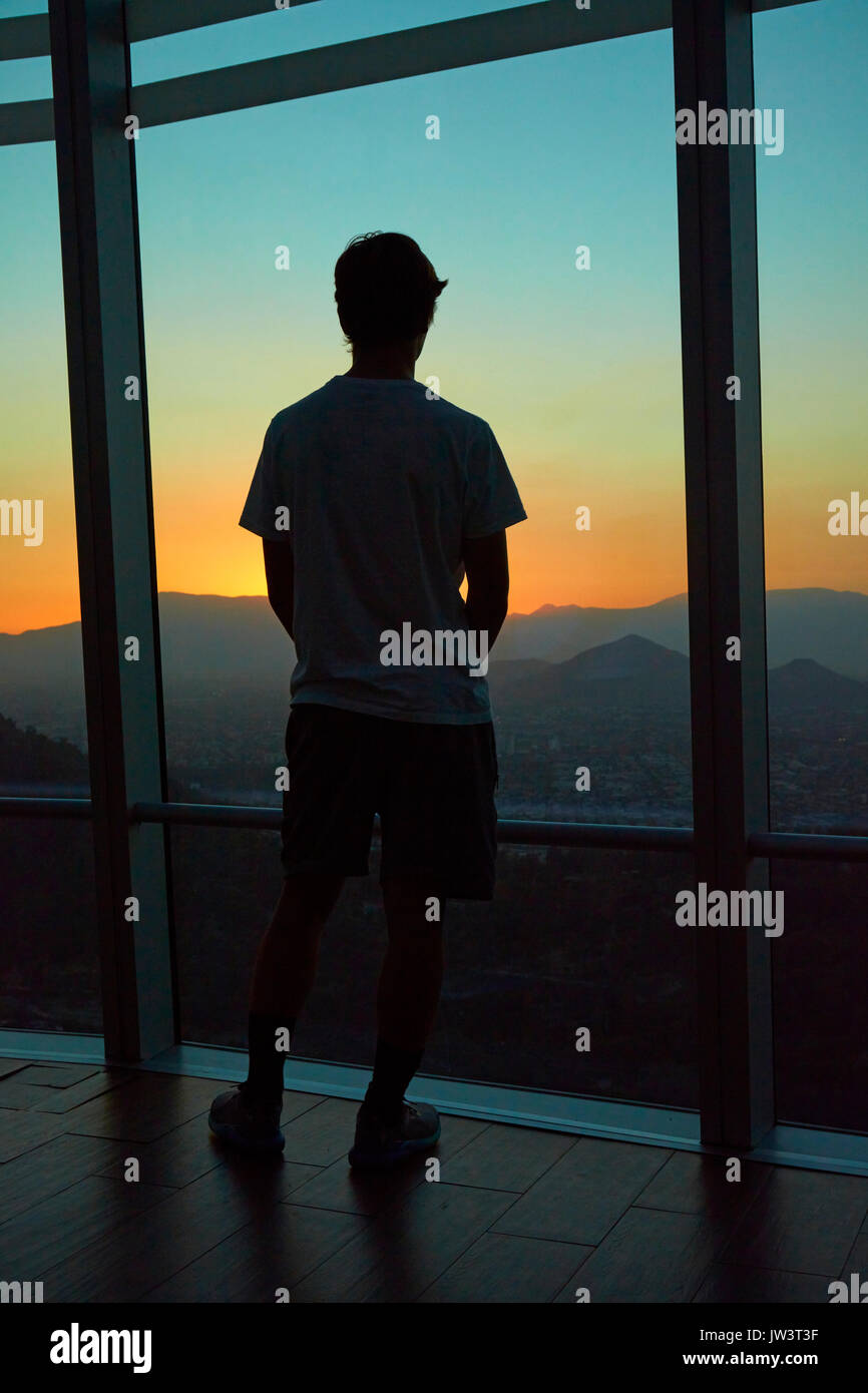 Tourist looking at the view at sunset from Sky Costanera skyscraper, Santiago, Chile, South America (model released) - Stock Image