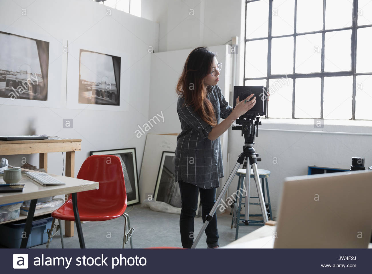 Female photographer adjusting camera lens in art studio - Stock Image