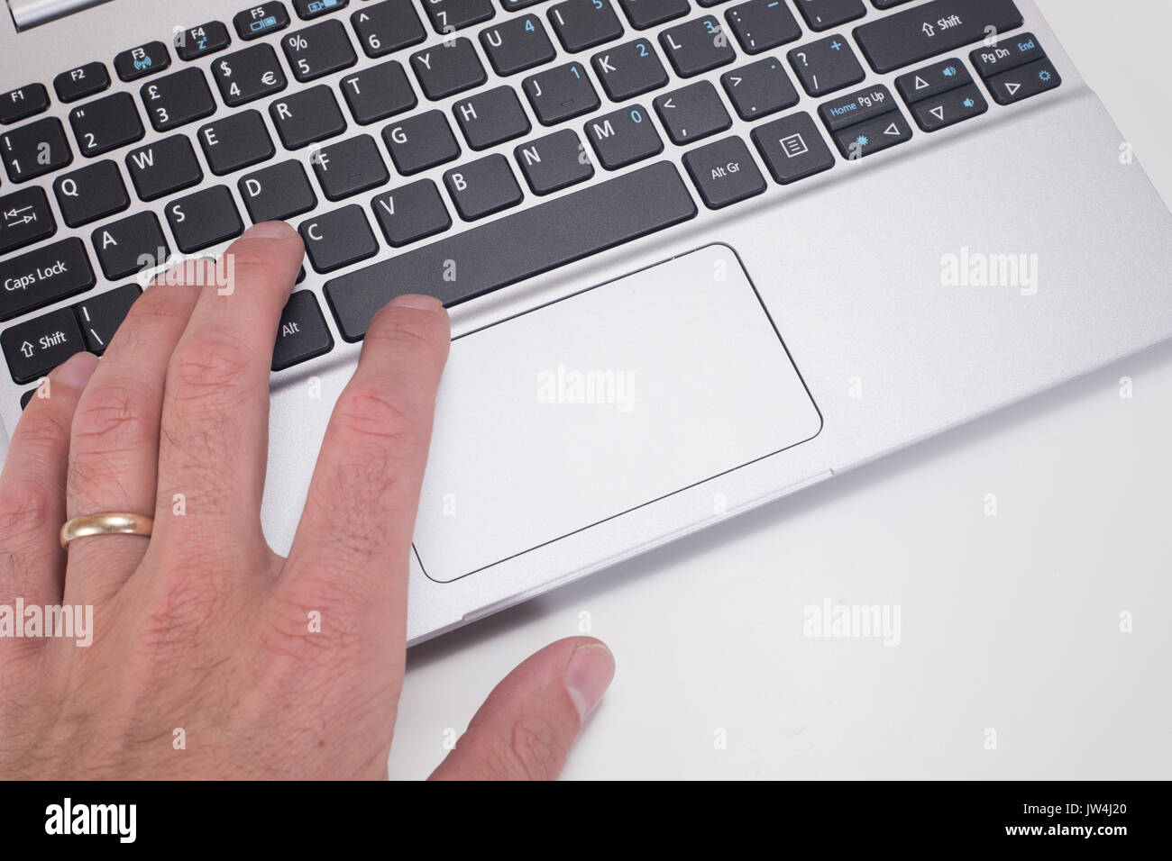 A mans hand with wedding ring using and pressing buttons on a computer laptop keyboard with white copy space. - Stock Image