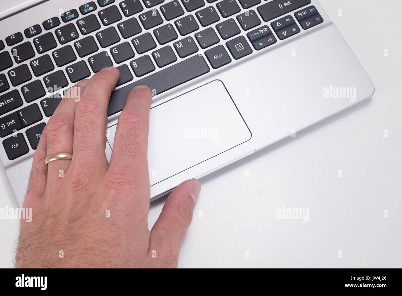 A mans hand with wedding ring using and pressing buttons on a laptop computer keyboard with white copy space. - Stock Image