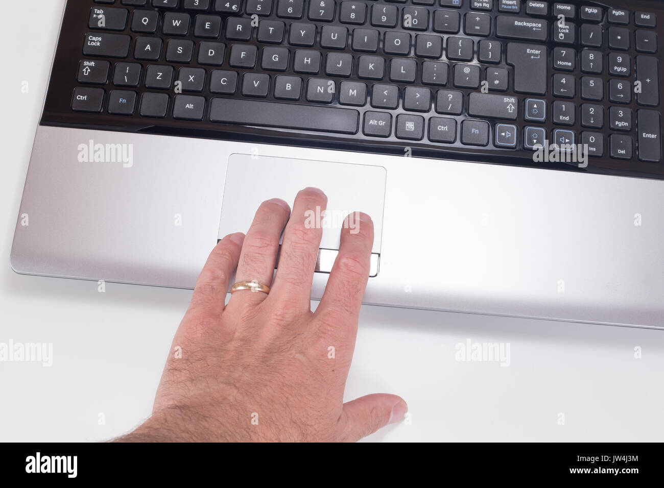 Close up of a mans hand with wedding ring using a tracking pad on a computer laptop with white background and copy space. - Stock Image