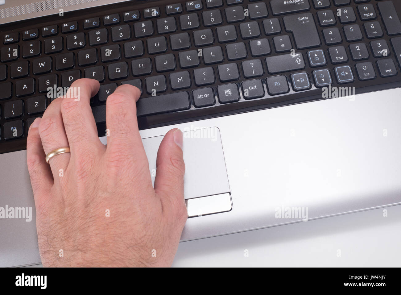 A close up of a mans hand with a wedding ring typing on a laptop computer keyboard. - Stock Image