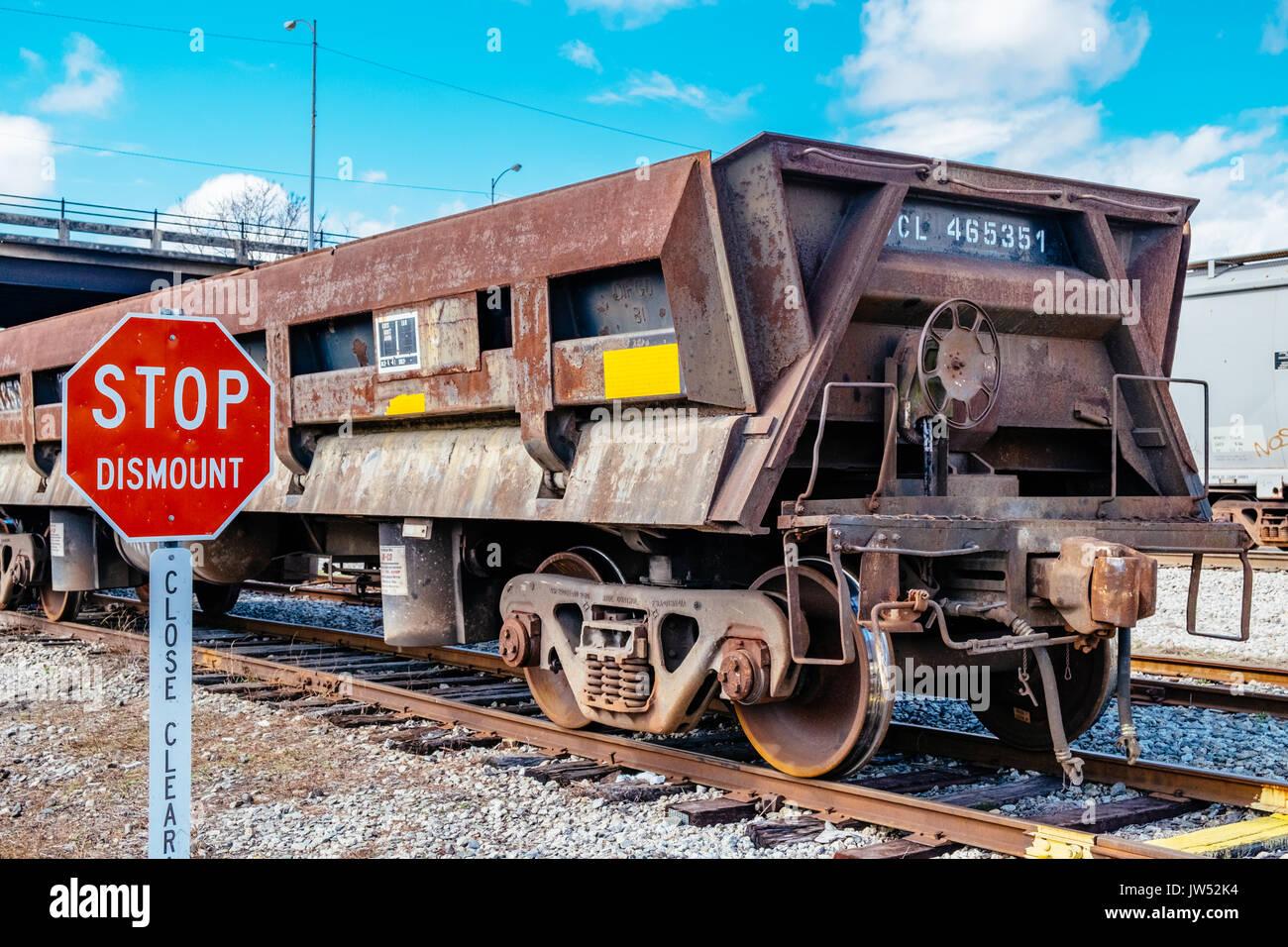 Rusted empty gondola railroad car, sitting on a siding spur in Opelika, Alabama, USA. - Stock Image