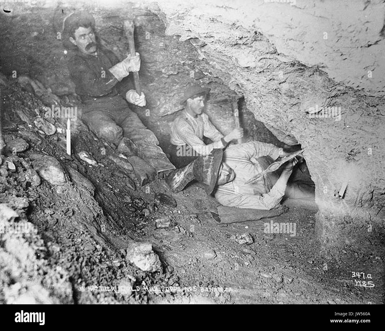 Three miners using pickaxes in underground gold mine lit by candlelight, Gold Hill, Yukon Territory, ca 1898 (HEGG 515) - Stock Image