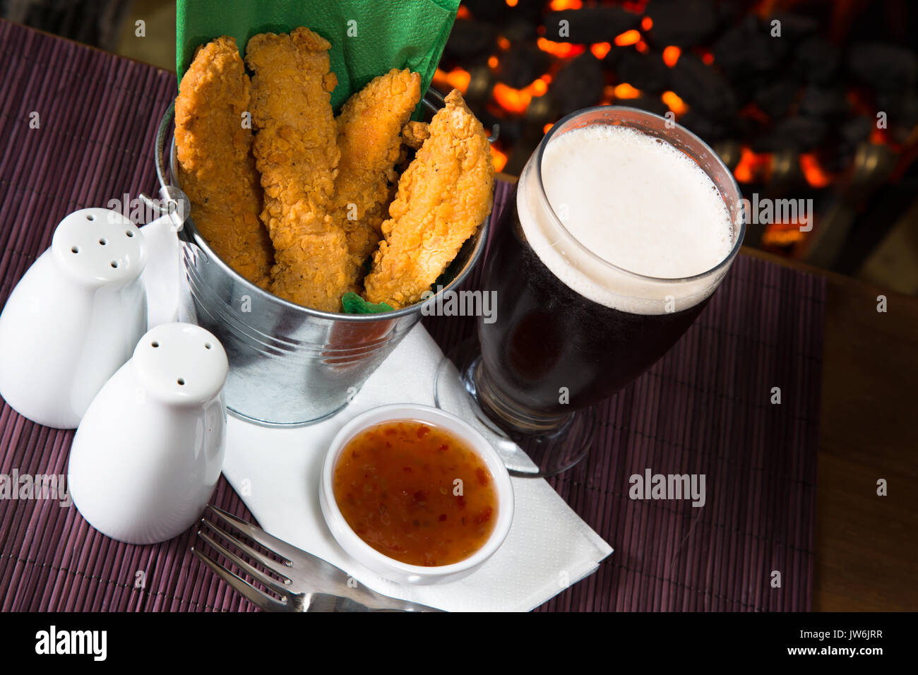 A pub/restaurant lunch/ snack of Hot and Spicy breaded Chicken fillets with a Sweet Chili dip and a glass of ale. - Stock Image