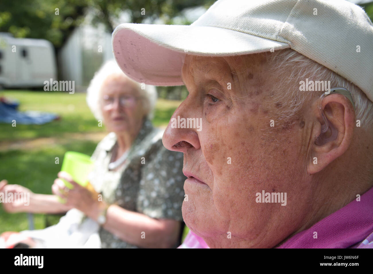 Elderly man wearing hearing aid, outdoors, England, UK - Stock Image