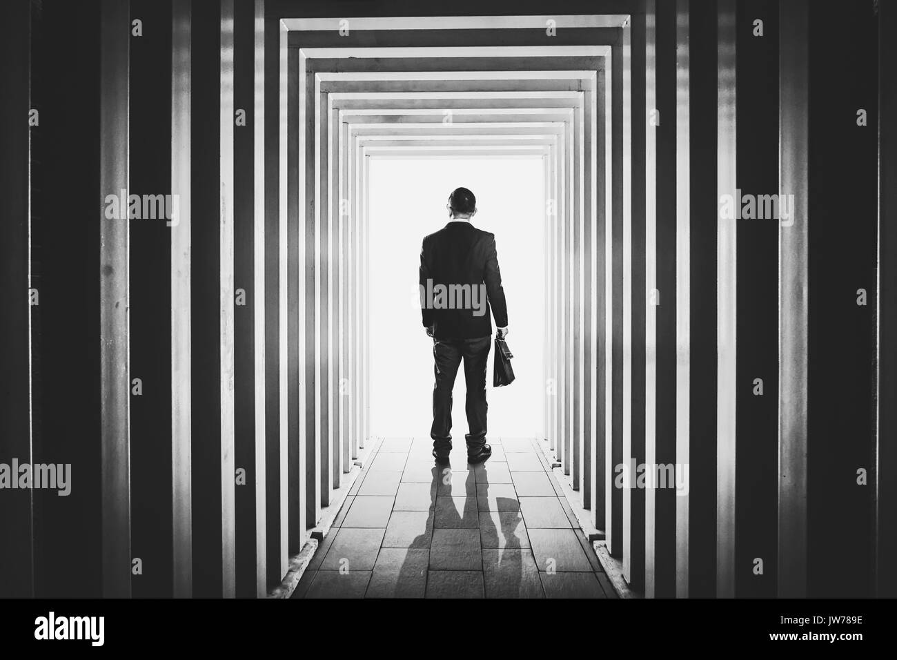 Businessman in line-shaped corridors and confused to exit the unknown bright door . - Stock Image
