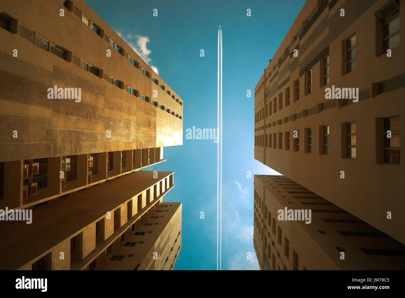 Airplane contrail against clear blue sky with abstract low angle view of common modern business skyscrapers. - Stock Image