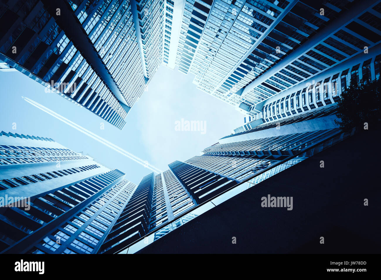 Airplane contrail against clear blue sky with abstract low angle view of common modern office skyscrapers. - Stock Image
