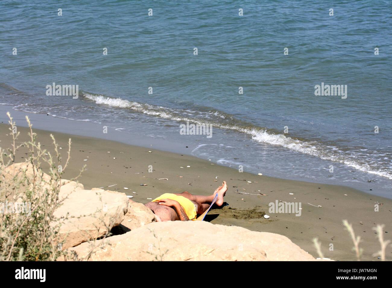 Sunbather on Beach - Stock Image