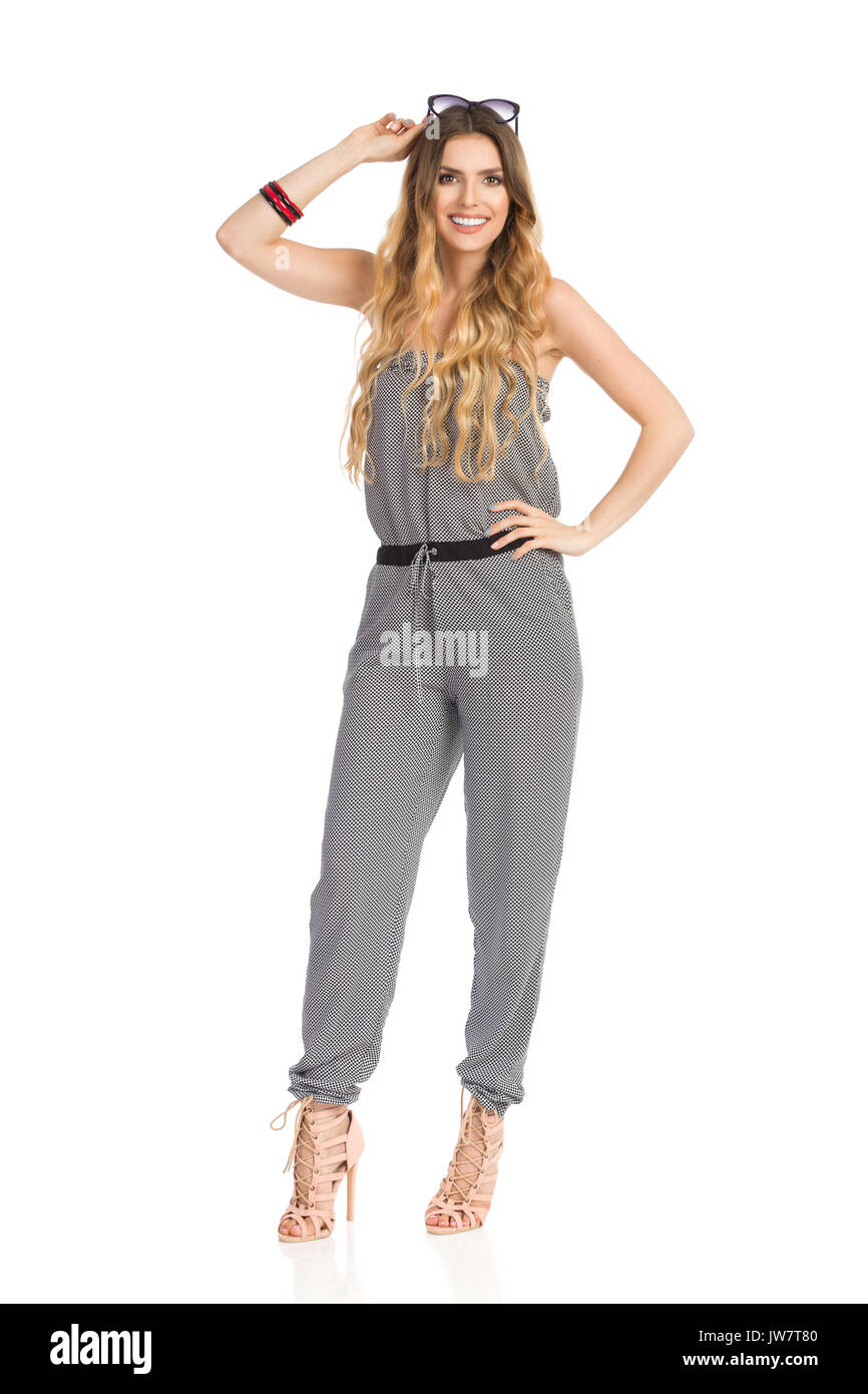 Smiling beautiful young woman in dotted jumpsuit and high heels is standing, holding sunglasses on head and looking at camera. Full length studio shot - Stock Image