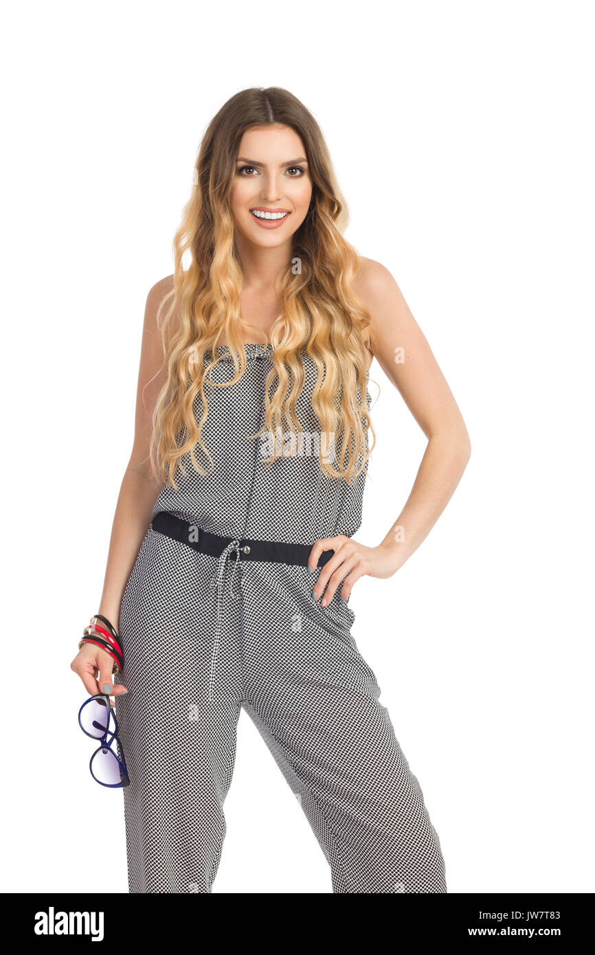 Smiling beautiful young woman in dotted jumpsuit is standing with hand on hip, holding sunglasses and looking at camera. Three quarter length studio s - Stock Image