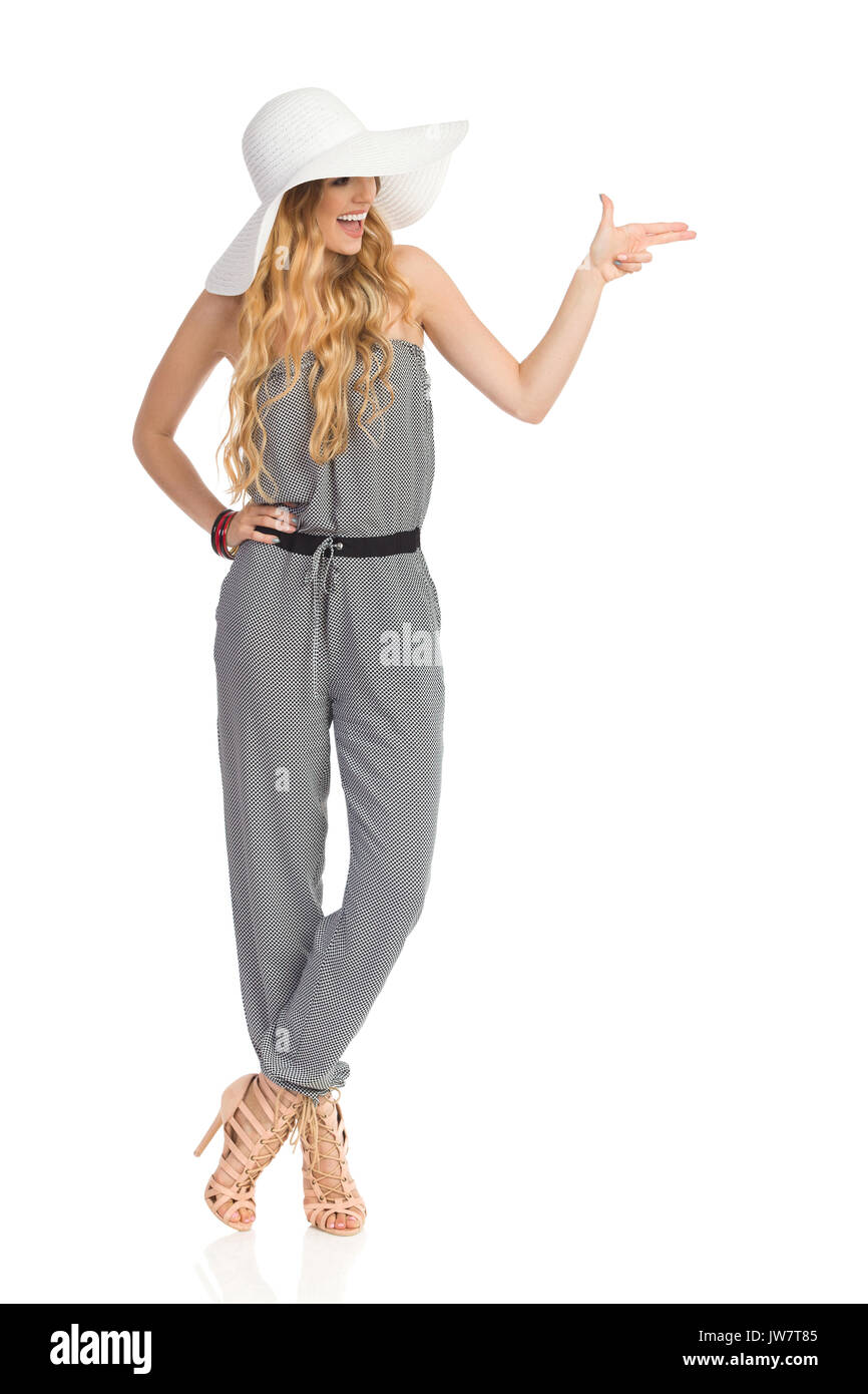 Happy beautiful young woman in dotted jumpsuit, white sun hat and high heels is standing with legs crossed, looking away, pointing and shouting. Full  - Stock Image