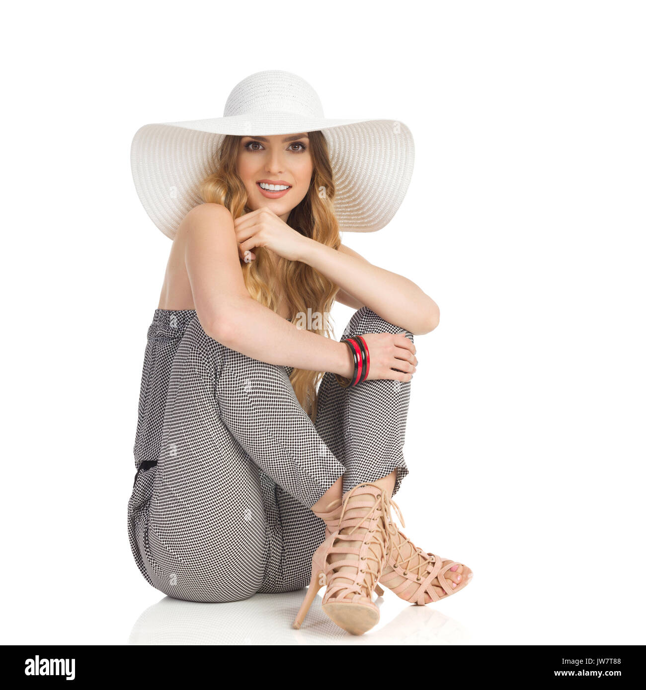 Young beautiful woman in jumpsuit, high heels and white sun hat is sitting relaxed on floor, smiling and looking at camera. Full length studio shot is - Stock Image