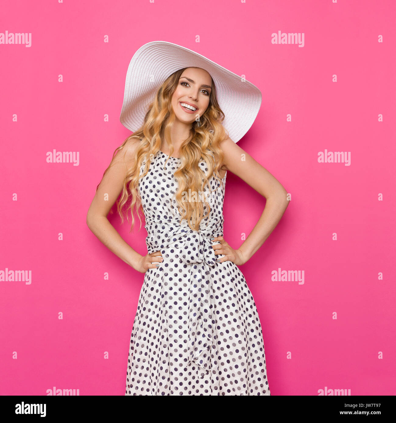 ced4a859b3bb Beautiful young woman in white dotted summer dress and sun hat is standing  with hands on