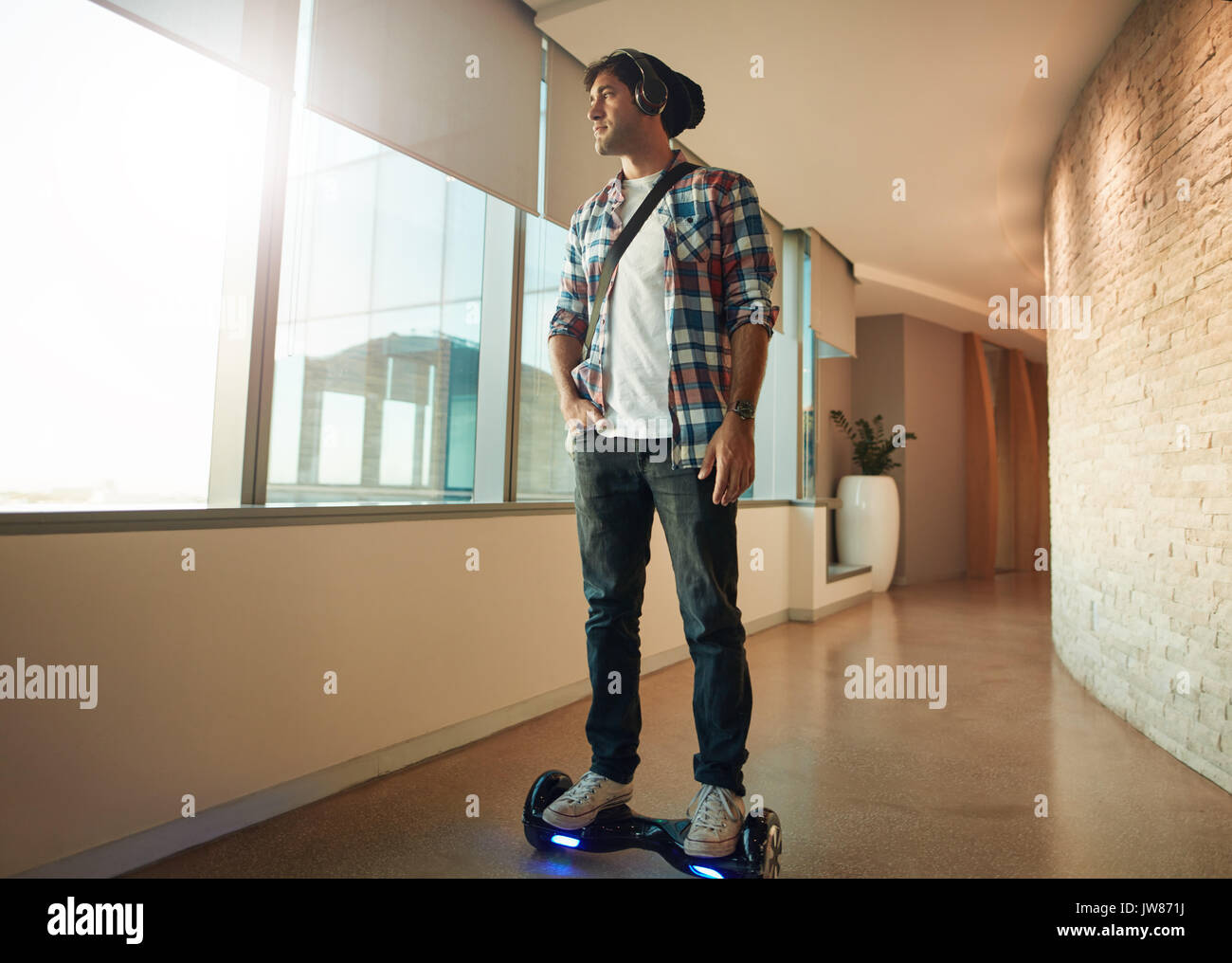 Indoor shot of young man riding on self-balancing electric scooter in office. Creative professional on hover board. - Stock Image
