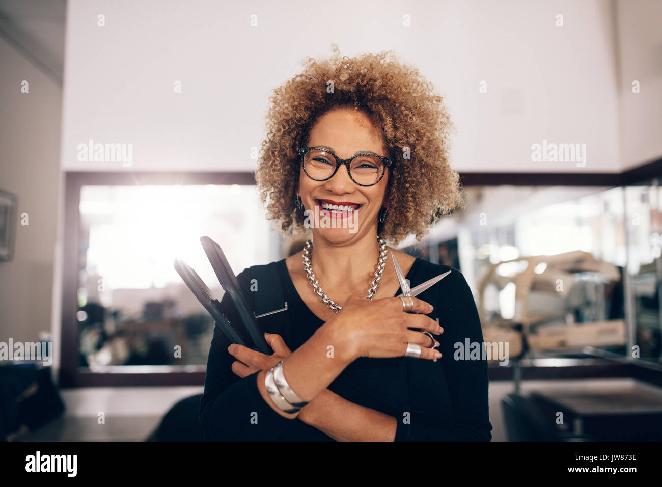Hairdresser holding a hair straightener and scissors. Closeup of curly haired woman hairdresser in happy mood at the salon. - Stock Image