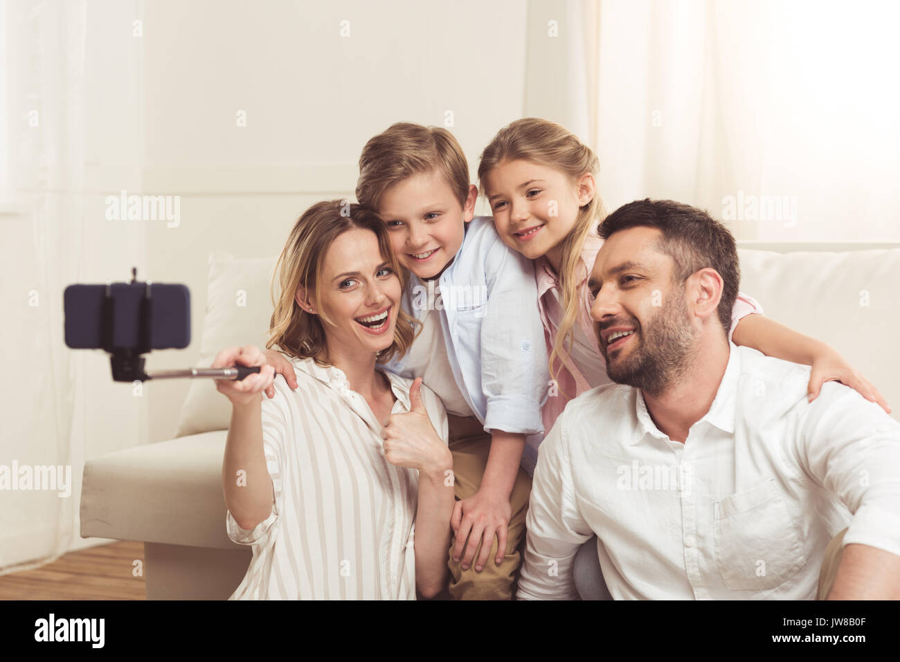 happy family taking selfie on smartphone with monopod at home - Stock Image