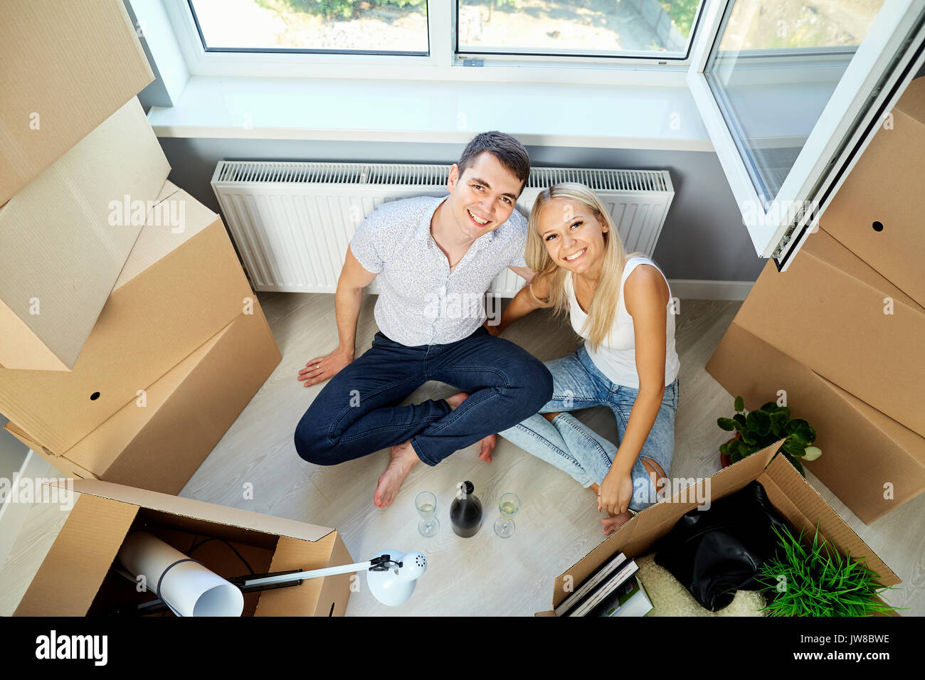 Happy couple with champagne in room for a housewarming. - Stock Image