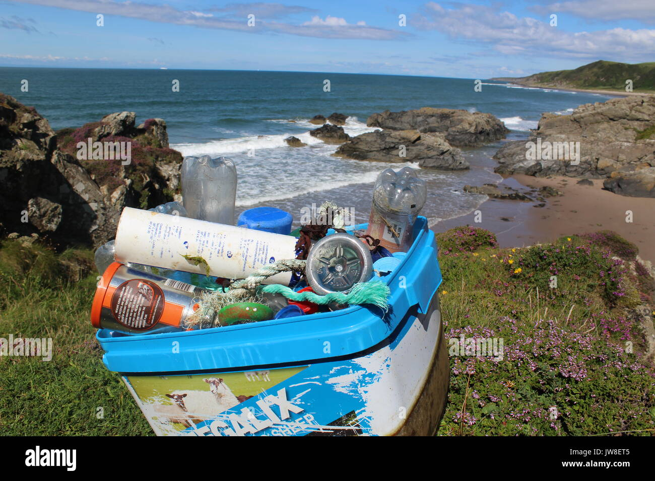 Pile of plastic rubbish cleaned from Killintringan beach in Dumfries and Galloway with rubbish in foreground and beach and blue skies in background - Stock Image