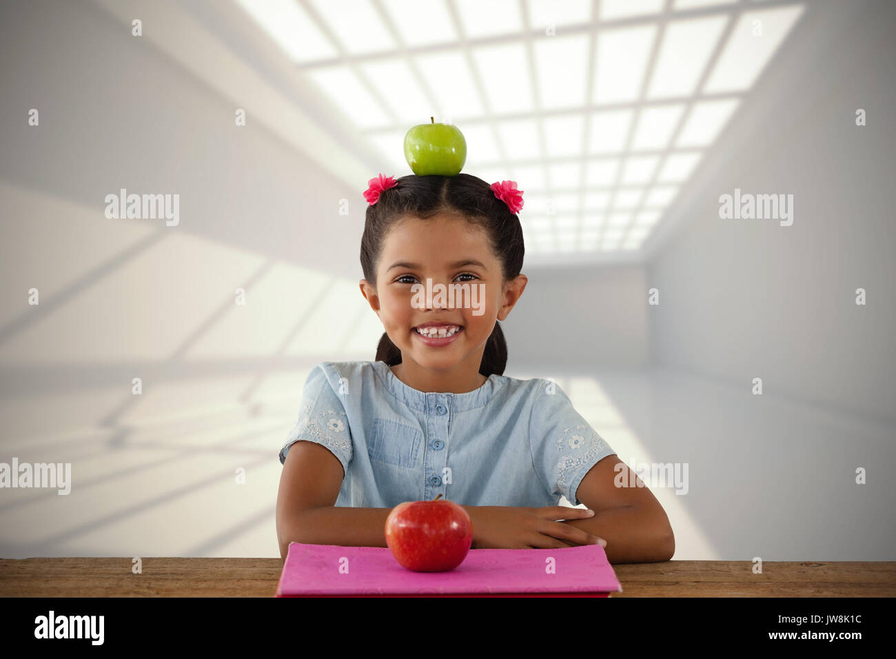 Smiling girl with Granny Smith apple on head against room with windows at ceiling - Stock Image