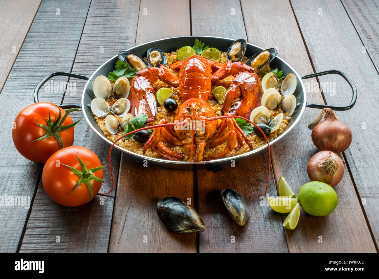 Gourmet seafood Valencia paella with fresh langoustine, clams, mussels and squid on savory saffron rice with peas Stock Photo