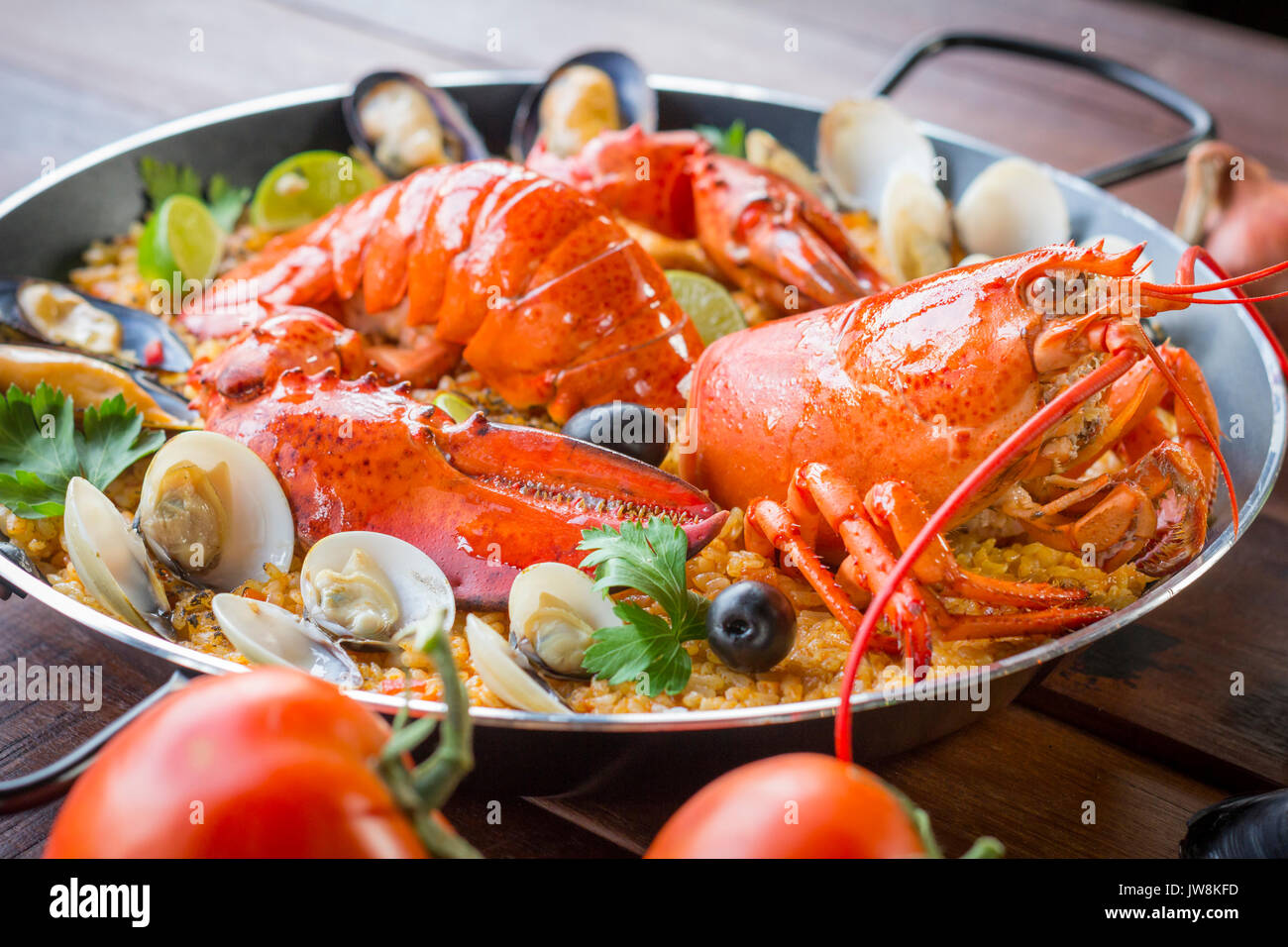 Gourmet seafood Valencia paella with fresh langoustine, clams, mussels and squid on savory saffron rice with peas and lemon slices, close up view - Stock Image
