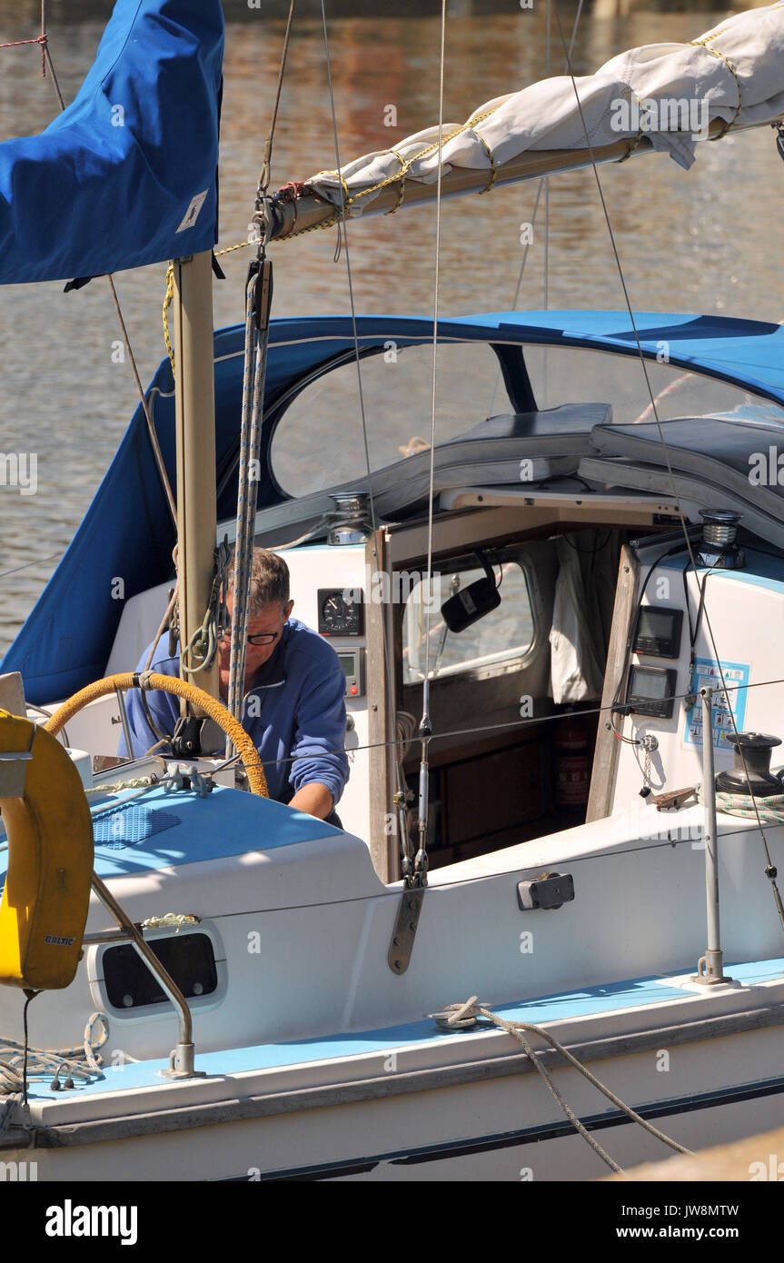 a man on a sailing boat yacht fixing or mending boat. - Stock Image