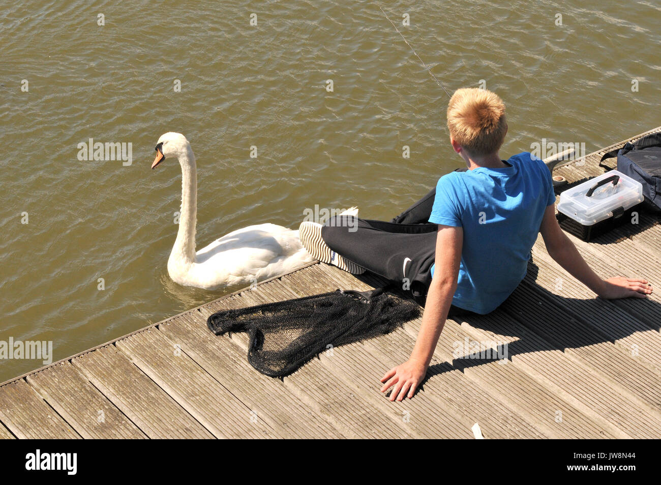 a young lad or boy sitting next to a river fishing next to some boats and swans contented and happy enjoying the sunshine and having fun - Stock Image